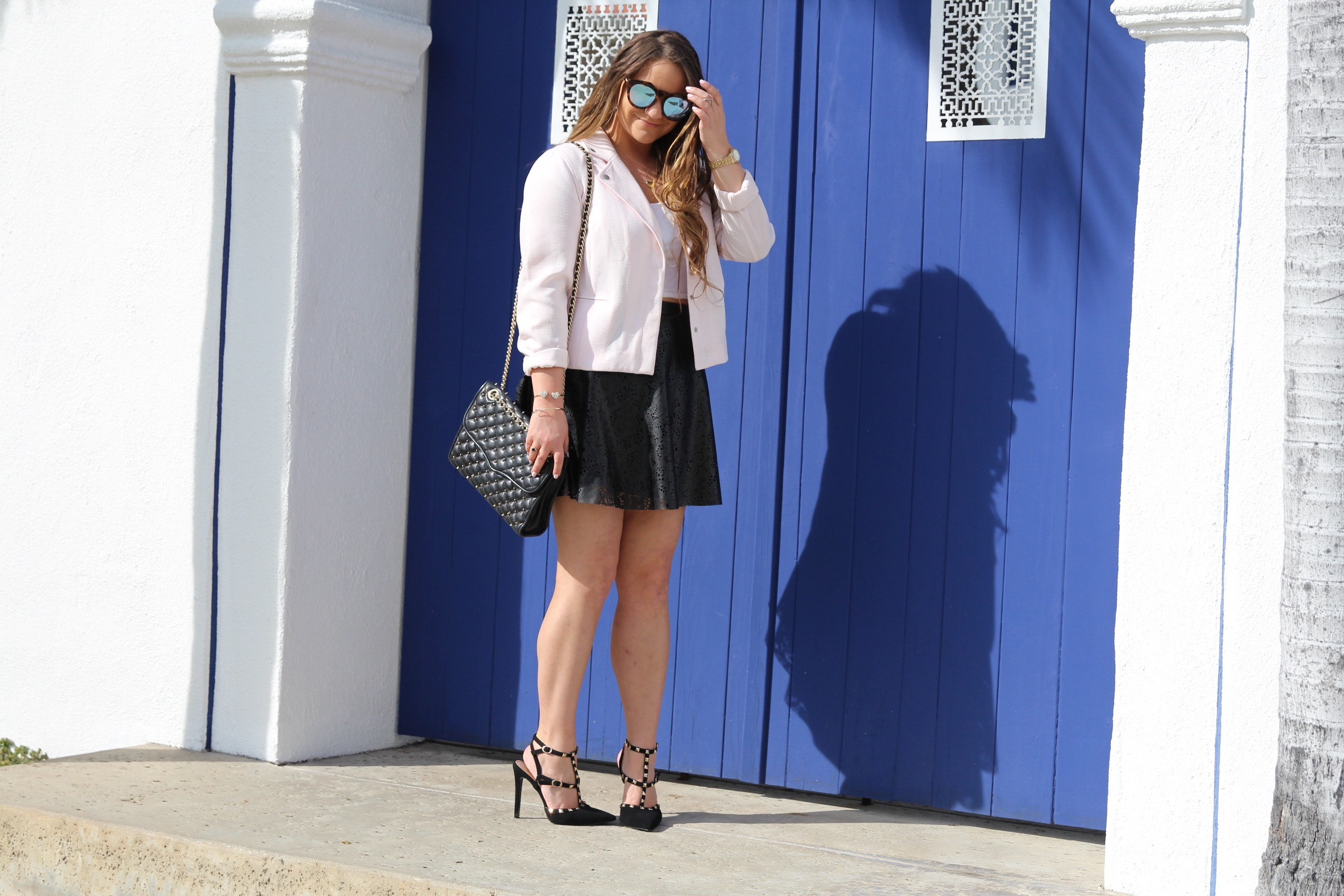 missyonmadison, fashion blog, fashion blogger, perforated skirt, black leather skirt, white crop top, white short sleeve crop top, light pink moto jacket, black studded heels, rockstud heels, look for less, le specs sunglasses, mirrored sunglasses, brunette hair, summer style, how to style a moto jacket, how to wear a leather skirt, la blogger, la style, melissa tierney,